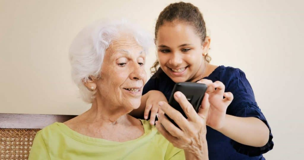 Granddaughter demonstrating social media to great-grandmother
